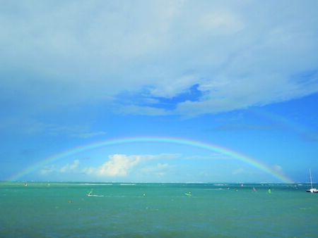 Rainbow over Caribbean sea with turquoise waters and blue sky with white clouds. Tropical landscape