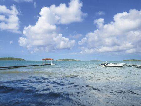 Wooden jetty in turquoise waters with waves. Blue sky with white Caribbean clouds. White boat moored. Tropical landscape. Stockfoto