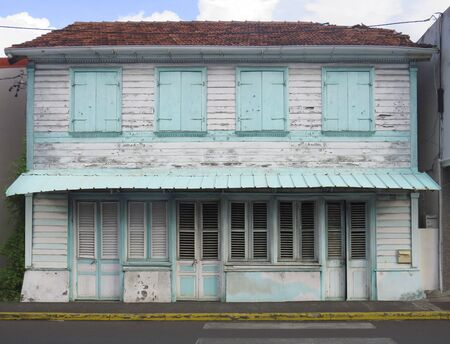 Typical wooden and rusted house in Martinique, French West Indies. Tropical blue and white windows Stockfoto