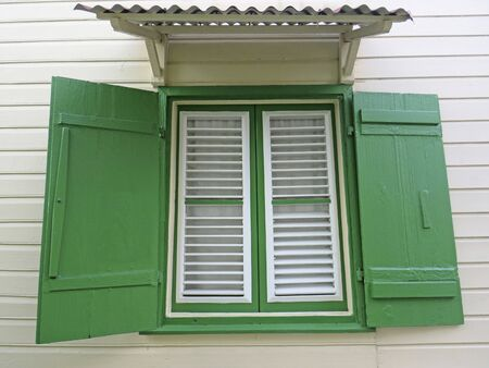 White wooden window, green shutters and sheet roof on the exterior of a white house. Vintage green window shutters. Caribbean architecture Stockfoto