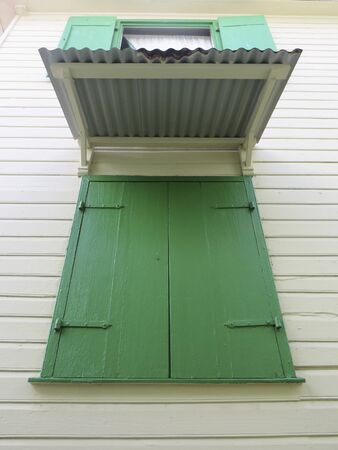 Closed and opened vintage green window shutters and sheet roof.