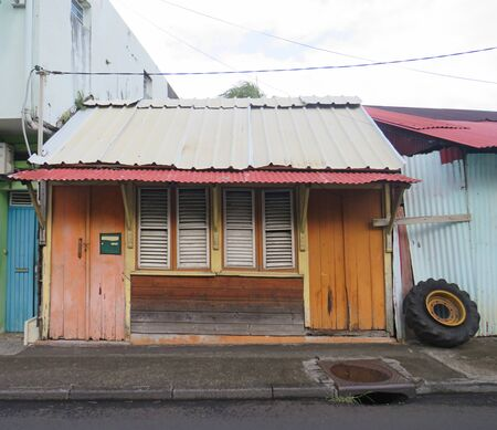 Caribbean wooden house with orange doors, tin roof and closed white window shutters. Caribbean architecture.