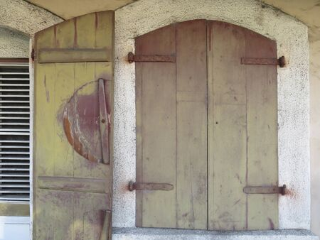 Closed and opened wooden vintage window shutters on stone wall. Caribbean architecture.