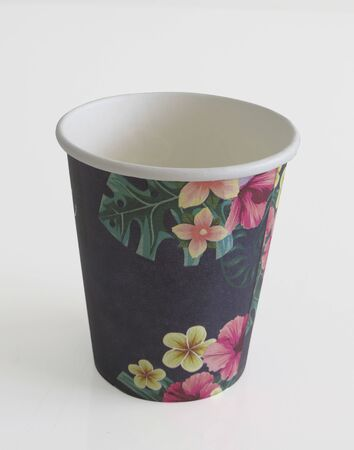 Isolated black takeaway disposable cup painted with Caribbean flowers on white background. Stockfoto