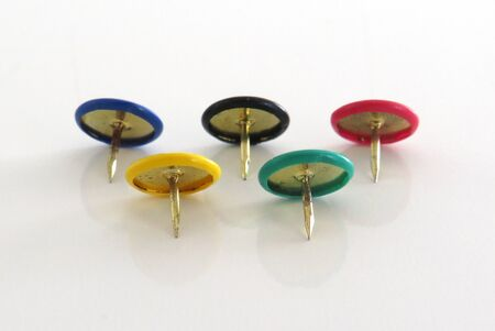 Pins of various colors on a white background. Rings of an  flag made  flat pins plastic round head