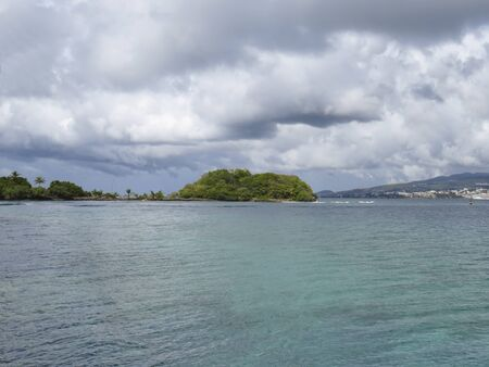 Turquoise waters of the Caribbean Sea and small islet with Caribbean vegetation. Tropical storm sky. Idyllic tropical landscape. Stockfoto