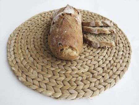 Delicious baked and cut fresh bread on handmade round beige wicker tablecloth isolated on white background. Freshly bread slices. Stockfoto