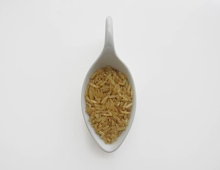 Organic raw Brown Rice in a white spoon on white background, top view. Integral Wholegrain. Stockfoto