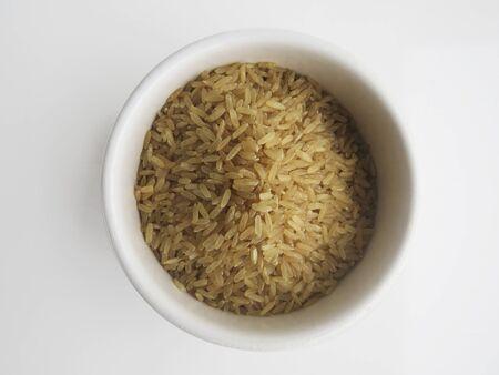 Organic raw Brown Rice in a white bowl on white background, top view. Integral Wholegrain. Stockfoto