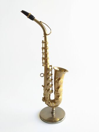 Close-up of elegant saxophone on white background. Side view of an extraordinary wind instrument for music lovers, instinctively creates melodious and soothing music commonly associated with jazz.