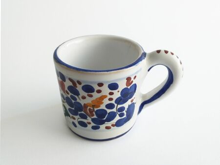 Aerial view of elegant painted ceramic mug with blue and grenade decorative elements on white background.