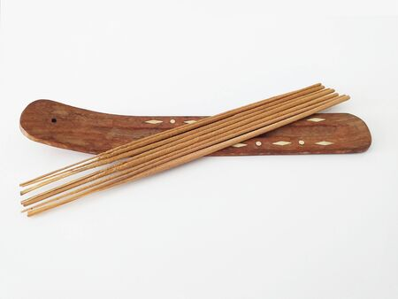 Aerial view of natural incense sticks on rectangular wooden censer isolated on white background.