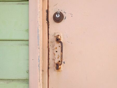 Close-up of pale pink rusty Caribbean house door, door handle, lock and light green wooden facade. Tropical Construction and Architecture. Martinique, Antilles. French West Indies. Stok Fotoğraf