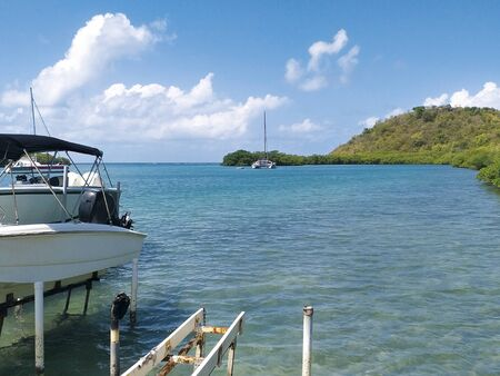 Turquoise waters of the Caribbean Sea with pleasure boats and lush vegetation. Idyllic tropical landscape.