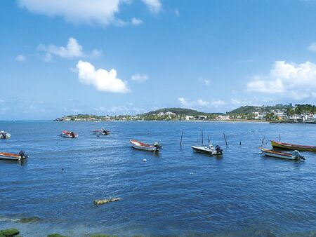 Turquoise waters of the Caribbean Sea with traditional fishing boats and the silhouette of a small town in the background. Idyllic tropical landscape. Authentic Caribbean spot. Imagens