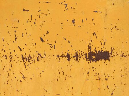 Peeling paint and rusty old metal background. Mustard colored rusty metallic abstract background. Patterns and texture. Stockfoto