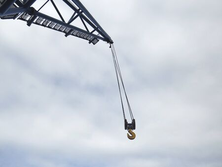 Close up of hanging crane hook and white cloudy sky. Industrial scene.Tall crane boom at construction site.