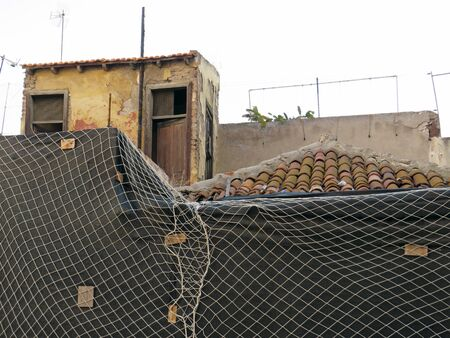 Ruined house undergoing rehabilitation with security mesh. Urban construction in poor condition background. Old destroyed house.
