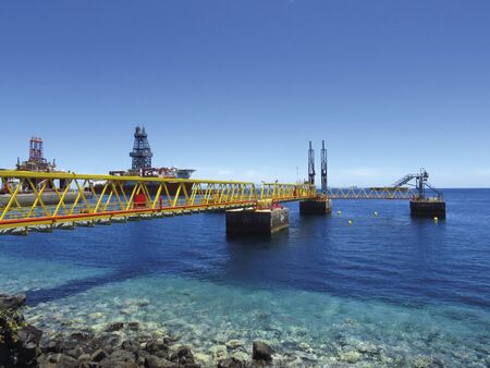 Industrial footbridge over crystalline waters, oil platform in maintenance and OFFSHORE oil activities. Maritime and industrial background.