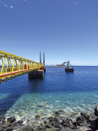 Industrial footbridge over crystalline waters in OFFSHORE oil activities port. Maritime and industrial background.