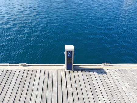 Coastal system for charging boat batteries and filling tanks with water. Station for refueling boats with water in the port. Electric panel for servicing and charging yachts