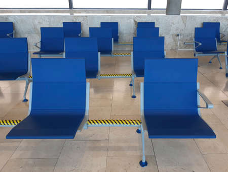Rows of empty blue seats in airport terminal. Contemporary lounge with seats in the airport, blue tone. Bench in the terminal of airport. Empty airport terminal waiting area with chairs.