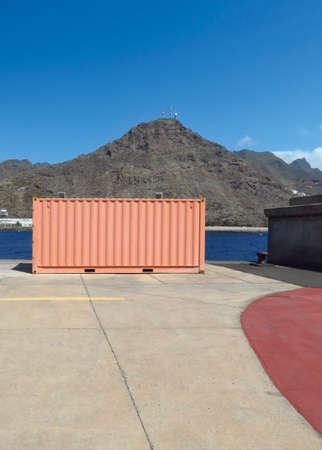 Sea freight container in industrial dock, volcanic mountain background and blue sky. Rectangular container for the transport of goods waiting for shipping. Maritime logistics background. 版權商用圖片