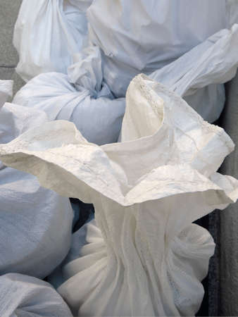 Detail of White debris raffia sack. White Canvas Membrane Plastic Bags With Construction Trash. Pile of plastic rubble sacks in the street. Works and constructions pattern.