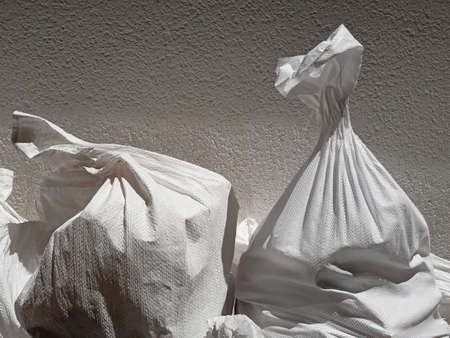 Front view of two White debris raffia sack. White Canvas Membrane Plastic Bags With Construction Trash. Works and constructions pattern.
