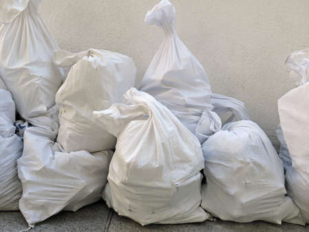Pile of plastic rubble sacks in the street.White debris raffia sack close up. Works and constructions pattern. White Canvas Membrane Plastic Bags With Construction Trash.
