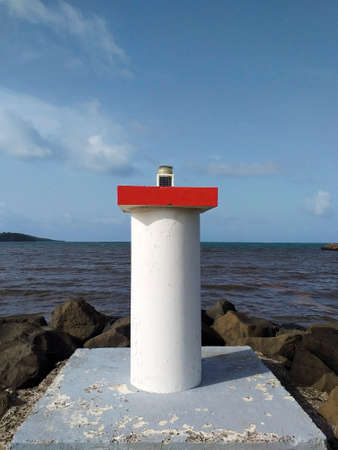 Port entrance signaling light. Entrance through Bocana with red port side marking light. Maritime and night navigation signals. Maritime beacon system.