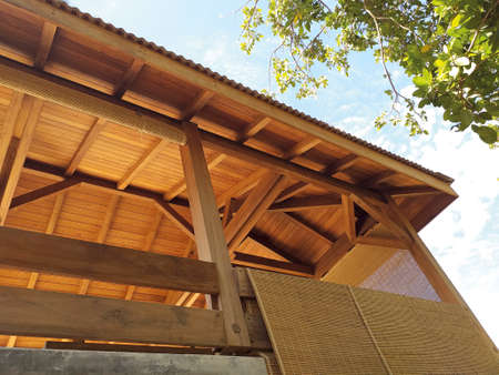 """Perspective view of a deck frame, known in French as """"charpente"""" in Caribbean construction. Spruce wooden structure at the interior of a roof. Detail of sustainable and ecological architecture. Zdjęcie Seryjne"""
