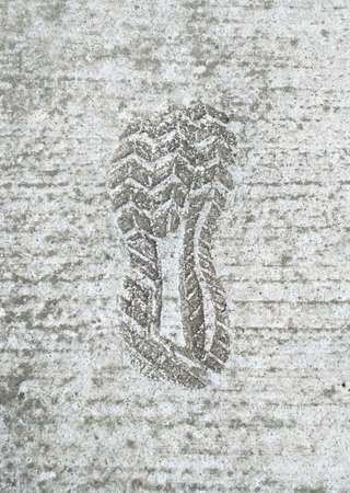 Grunge textured concrete sidewalk shoe foot print. Front view of footprint of shoe sole on concrete floor.