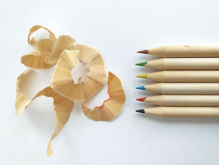 Overhead view of graphite pencil shavings with different colored tip pencils isolated on white background. Pencil sharpener waste, wood chips and crayons background. School supplies and back to school pattern.