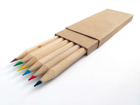 Colored tipped wooden pencils inside recycled paper case isolated on white background. Crayons with eco-friendly cover close up. School supplies and back to school pattern.