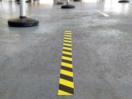 Yellow and black passage and space delimiting strip on gray ground. Covid 19 prevention self-adhesive sign close up. Information, prevention, prohibition and warning signs concept.