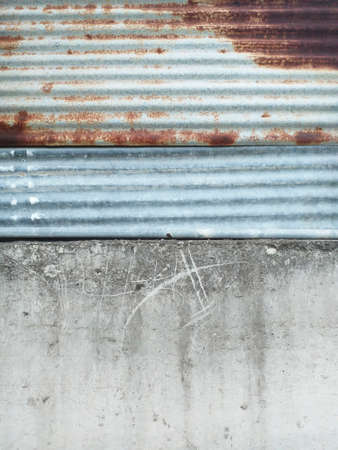 Rusty aluminum metal fence texture on old and worn gray concrete wall. Tropical construction. Detail of tropical architecture. Aged Corrugated Rusty Metal Texture