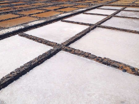 Perspective view of salt evaporation ponds, also called salterns or salt pans. Pits or crystallizers with stagnant water for the production of salt. Salt drying, Salar pans or salinas background. 版權商用圖片