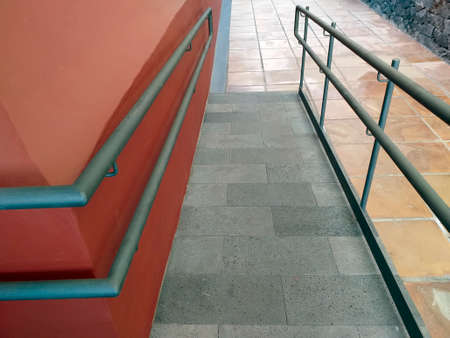 Access ramp to the building for the disabled with handrails. External Disabled Accessible Ramp For Wheelchair Use. Adaptation of buildings concept. Architecture and construction detail.