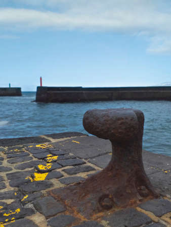 Rusty iron bollard on dock, harbor entrance and port and starboard signals. Nautical, ports and maritime navigation fund.