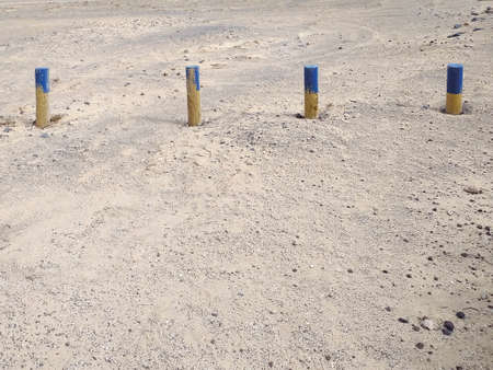 Line of wooden poles painted blue in the upper part delimiting the beach area. Wooden posts in a line delimiting the coastal area. Background of landmarks in the sand.