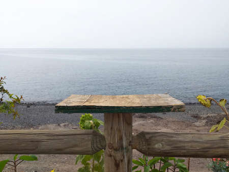 Original rustic wooden fence with horizontal board over the gray ocean. Volcanic and extreme landscape.