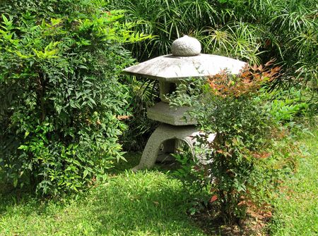 Stone Japanese lamp Yukimi-gata among greens in a garden                                photo