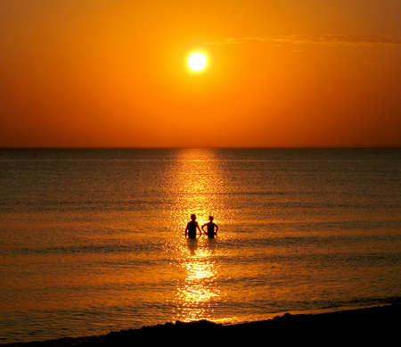 Two people at sunset in the sea                                photo