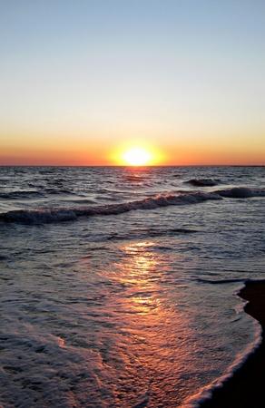 Sea wave covers the coast on a sunset photo