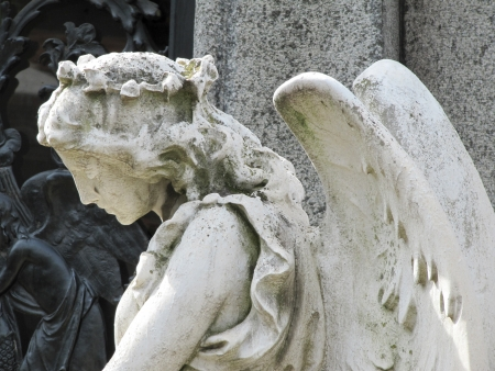 angel alone: Old statue of the sad Guardian angel. Mourning.                                 Stock Photo