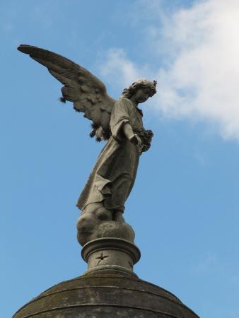 angel de la guarda: Antigua estatua de �ngel de la guarda en el cielo azul