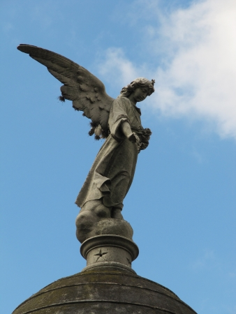 Old statue of Guardian Angel on blue sky