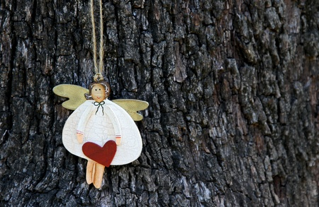 Wooden Angel with heart against tree bark  photo