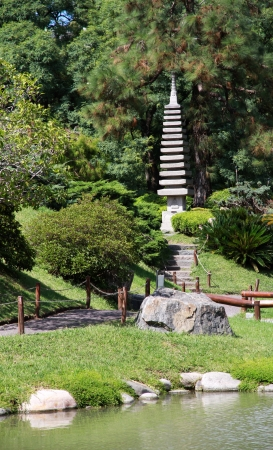 Japanese garden in the summer. Stone traditional tower .  photo